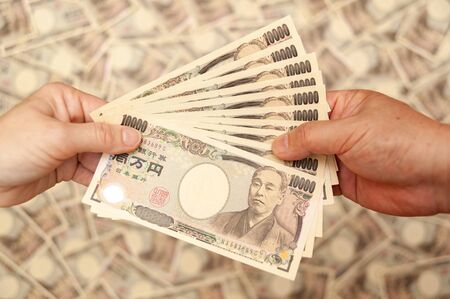 YEN - Japanese money: Hands holding (paying / receiving) 100,000 yen banknote. Isolated on blurred background of 10,000 yen notes. Close-up. Horizontal shot.