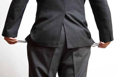 Bankrupt businessman showing empty pants pockets out. Concept: World economic crisis. Isolated on white background. Horizontal shot.