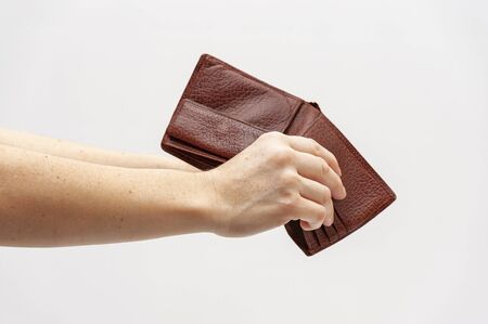 Close-up of hands holding brown leather wallet with no money. Concept: World economic crisis. Isolated on white background. Copy space. Horizontal shot.