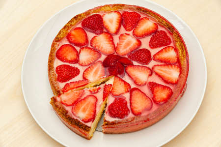Delicious homemade strawberry tart. Isolated on wooden background. Top view. Close-up. Horizontal shot. Imagens