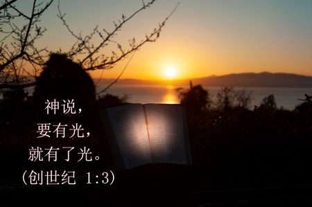 Holy Bible opened with directional light. Background with sea, golden sky and sunrise behind the mountains. Text in Chinese characters from Genesis chapter 1 verse 3. Copy space. Horizontal shot. Reklamní fotografie