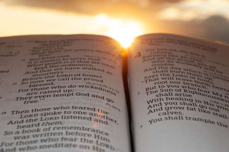 Holy Bible open at sunset with highlight on Malachi 4: 2. Background with clouds and sun.