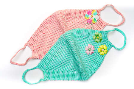 Handmade crochet face mask. Green and pink color with flower designs. Isolated on white background. Top view.