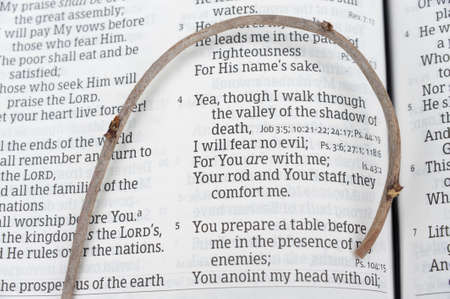 Holy Bible opened in Psalm 23 with a small staff on top. Highlighted on versions 3, 4 and 5. Close-up. Horizontal shot.