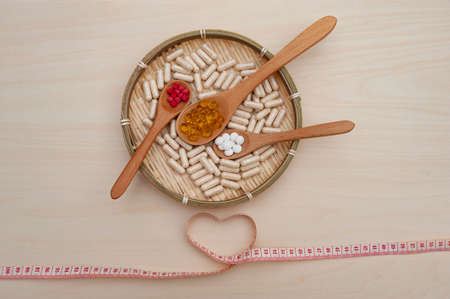 Healthy lifestyle - Vitamins, minerals and nutritional supplements in wooden spoons inside a braided bamboo plate with a heart shaped soft vinyl tape measure. Isolated on wooden background. Top view.