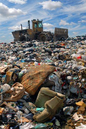 camion de basura: La excavadora entierra los alimentos y los desechos industriales