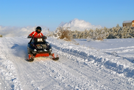 The man goes on a snowmobile on snow road Stock Photo