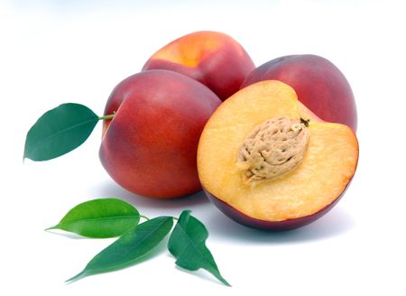 yellows: Smooth peaches and a half and leaves on a white background