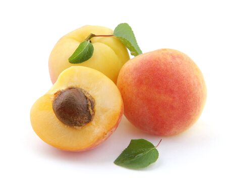 Apricots and a half on a white background