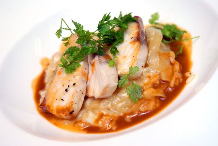 rizotto with a fried pike perch in sauce and with greens