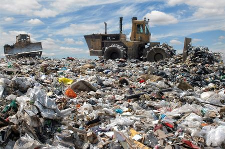 The bulldozer buries food and industrial wastes photo