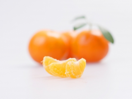 clementines: Three clementines with segments on a white background Stock Photo