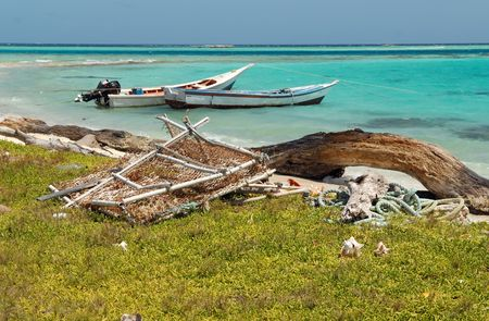 Two fishing boats at coast in Caribbean sea, a log and a trap for lobsters photo