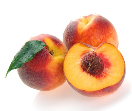 yellows: peaches and a half and leaves on a white background