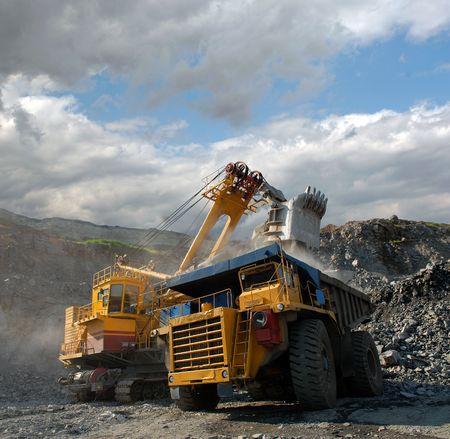 mijnbouw: Laden van ijzererts op zeer grote dump-body vrachtwagen