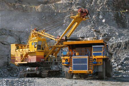 Loading of iron ore on very big dump-body truck photo
