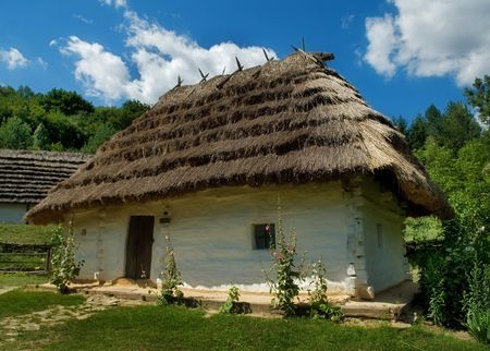 a house with a straw: The house with a straw roof in the Ukrainian village Stock Photo