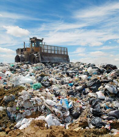 camion de basura: El bulldozer entierra alimentos y desechos industriales