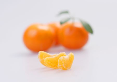 Three clementines with segments on a white background photo
