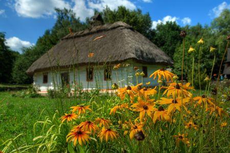 Ethnos, village, Ukraine, village, hut, flowers, summer, fence, landscape, the dark blue sky, clouds, a sunny day photo
