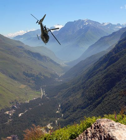 The helicopter flies in mountains of Caucasus
