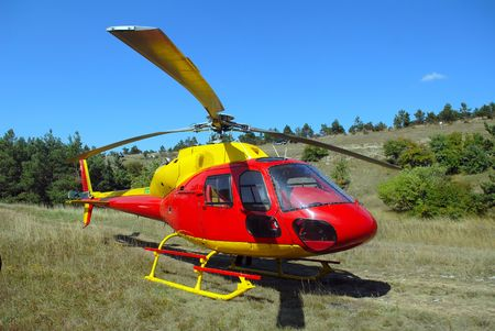 The helicopter has landed in mountains on a glade Фото со стока