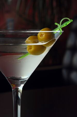 Two olives on a sword in a martini glass