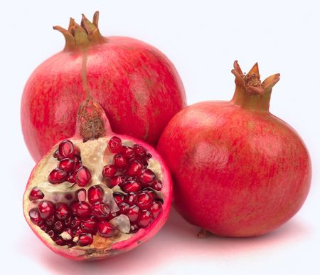 Pomegranate, whole and open-face with seeds  on a white background