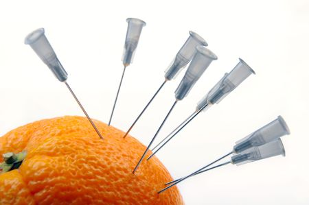 Needles from a syringe in an orange peel photo