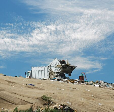 The garbage truck unloads dust on a dump photo