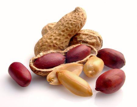 legumbres secas: Cacahuete en una shell y liquidado sobre un fondo blanco  Foto de archivo