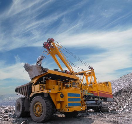 grab: Loading of iron ore on very big dump-body truck Stock Photo