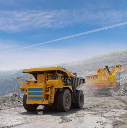 mining truck: Loading of iron ore on very big dump-body truck Stock Photo