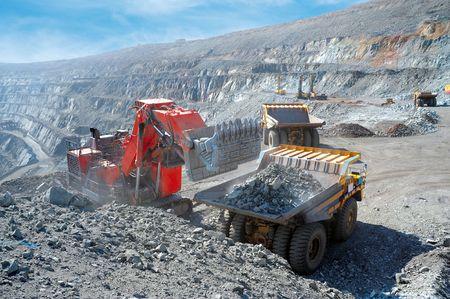 mining: Loading of iron ore on very big dump-body truck Stock Photo