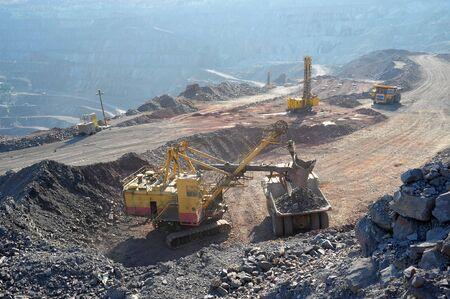 Loading of iron ore on very big dump-body truck Stock Photo