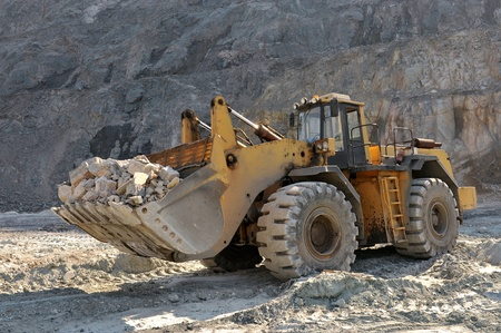 Wheel loader machine unloading rocks in the open-mine of iron ore Standard-Bild