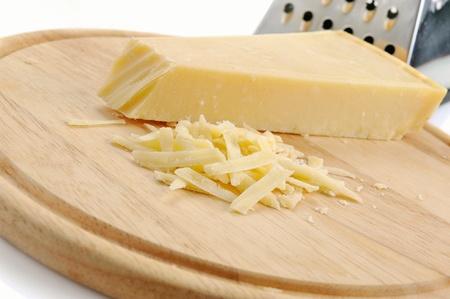 queso rayado: Bloque de queso parmesano con rallador de metal en la tabla de cortar de madera Foto de archivo