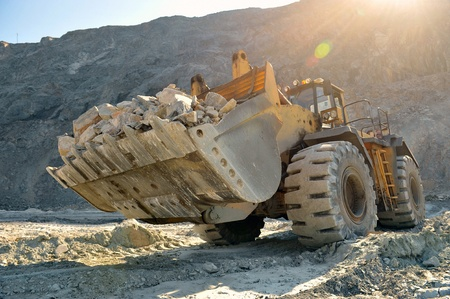 Wheel loader machine unloading rocks in the open-mine of iron ore Archivio Fotografico