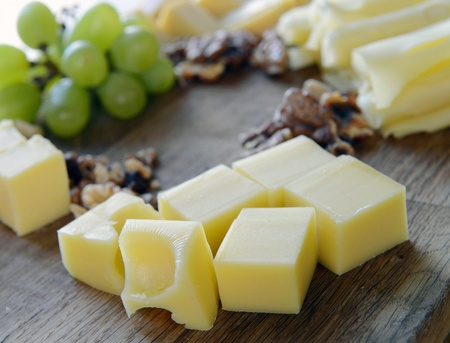 chees: set cheese on a wooden board with grapes and nuts Stock Photo