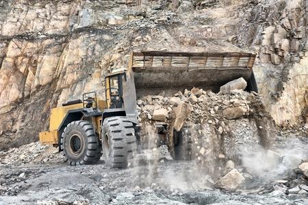 maquinaria pesada: De la máquina cargadora de ruedas descarga rocas al aire libre de las minas de mineral de hierro