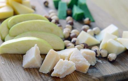 queso rallado: de queso parmesano con nueces y manzanas en una tabla de madera