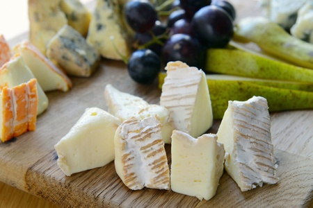 set of cheese with mold on a wooden board with grapes and pears Stock Photo - 13518381