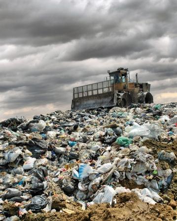 camion de basura: La excavadora entierra los desechos alimentarios e industriales