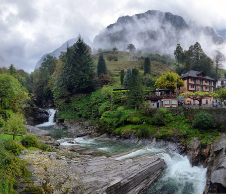 Swiss village in the mountains with mist and waterfall