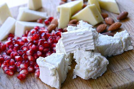 queso de cabra: conjunto de queso de cabra sobre una tabla de madera con una granada Foto de archivo