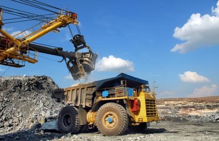 mining truck: La carga de mineral de hierro en vertedero muy grande-caja del camión