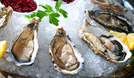 Fresh oysters platter with sauce and lemon served on a marble vase with ice Stock Photo