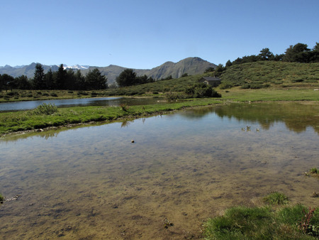 Small lake of Vielha. Landscape near the tunnel of Vielha, road N 230, Vielha e Mijaran, Viella, Val dAran, Aran Valley, Pyrenees, Lleida province. View of mountains, town centre, river and Vielha small lake photo