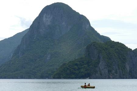 ボートで大きなトランクを持つ子供。