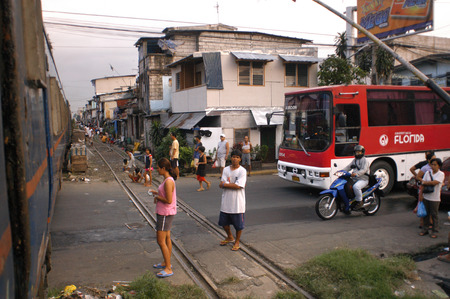 shanty: New coach bus. People living along the railway. Maninal train Station.  Slum dwellings in Blumentritt Manila. Rail track and squatters at Blumentritt Manila.